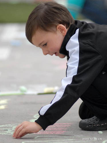 A child chalk-draws on the pavement during first Chalkupy Vancouver event in Vancouver, Canada, on September 22, 2012. People from all walks of life descend on Robson Street in downtown Vancouver at noon to create beautiful sidewalk chalk art together. Photo: Xinhua