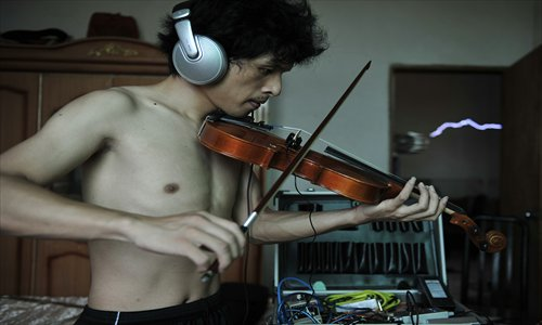 Wang Zengxiang, founder and leader of the band, experiments with a violin in his home. Photo: CFP