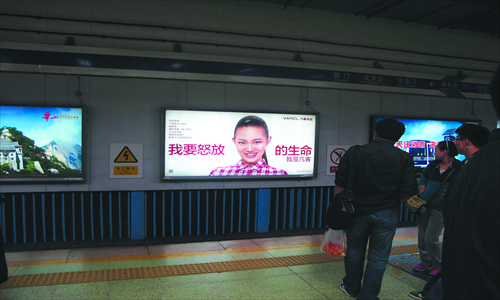 A commuter looks at a Vancl billboard in a subway station in Beijing Sunday. Photo: Li Qiaoyi/GT
