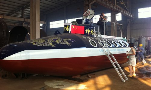A homemade submarine, Sacred Dragon 2, sits in a factory in Fuyang, Anhui Province, awaiting the installation of an electronic system before its trial run. Its maker, Zhang Junlin, a retired police officer, said the ship can dive 50 meters underwater and can move at a speed of 15 kilometers per hour, carrying 12 passengers. Zhang's previous masterpiece, Sacred Dragon 1, was much smaller and underwent its maiden voyage in September 2010. Photo: CFP