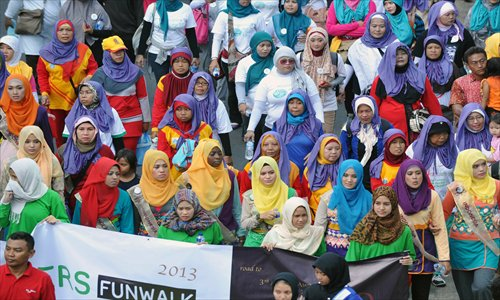 Contestants of the World Muslimah contest and members of the Indonesian Hijabers community, a female Muslim community whose members wear headscarves, take part in a fun walk in Jakarta on Sunday. The Muslimah World contest to be held on Wednesday in the Indonesian capital, Jakarta, is