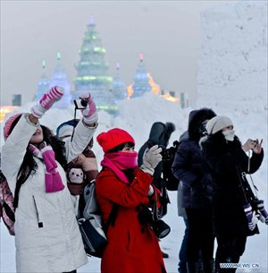 Tourists take photos of snow sculptures at the 29th Harbin International Ice and Snow Festival in Harbin, capital of northeast China's Heilongjiang Province, December 23, 2012. The festival kicked off at the Harbin Ice and Snow World on Sunday. Photo: Xinhua