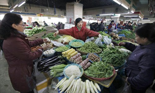 Consumers buy vegetable at a market in Nanjing, capital of east China's Jiangsu Province, December 9, 2012. China's consumer price index (CPI), a main gauge of inflation, grew 2 percent year on year in November, the National Bureau of Statistics announced Sunday. The inflation rate increased from a 33-month low of 1.7 percent in October as food prices increased. Photo: Xinhua