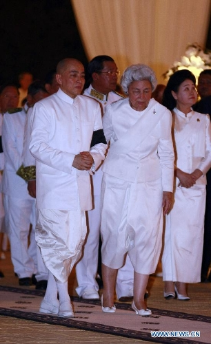Cambodia's Queen Mother Norodom Monineath Sihanouk (R, front) and King Norodom Sihamoni (L, front) leave the cremation site next to the royal palace in Phnom Penh, Cambodia, Feb. 4, 2013. Cambodia began to cremate the body of the country's most revered King Father Norodom Sihanouk on Monday evening after it had been lying in state for more than three months at the capital's royal palace. (Xinhua/Sovannara)