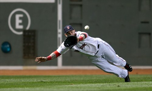Jonny Gomes of the Boston Red Sox catches a ball hit by Matt Adams of the St. Louis Cardinals in the fifth inning of game one of the 2013 World Series at Fenway Park on Wednesday in Boston. Boston defeated St. Louis 8-1. Photo: AFP