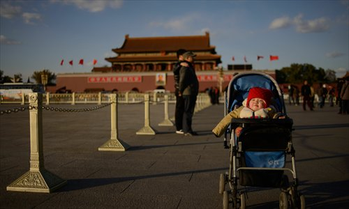 A baby sits in a pram on Tiananmen Square in Beijing on Sunday. On Friday the Communist Party of China announced an easing of the country's controversial family planning policy as part of a raft of sweeping pledges including the abolition of its re-education through labor system and loosening controls on the economy. Photo: AFP