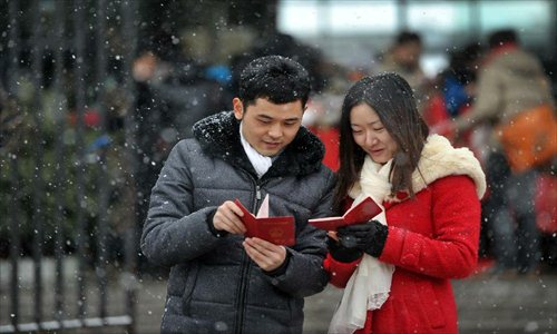 A couple look at their marriage certificates after registering in the marriage registration office in Furong district of Changsha, capital of Central China's Hunan Province, January 4, 2013. Quite a number of couples flocked to tie the knot on January 4, 2013, or 2013/1/4, which sounds like