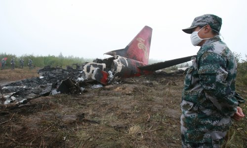 Soldiers guard the remains of a crashed plane on August 25, 2010. The plane, which belonged to Henan Airlines, had crashed while landing at an airport in Yichun, Heilongjiang Province the previous night. Photo: CFP