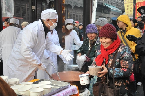Citizens get free porridge at a Chinese herbal medicine store in Hangzhou, capital of east China's Zhejiang Province, Jan. 19, 2013, to celebrate the traditional Laba Festival. Laba literally means the eighth day of the 12th lunar month. The Laba Festival is regarded as a prelude to the Spring Festival, or Chinese Lunar New Year, the most important occasion of family reunion, which falls on Feb. 10 this year. Eating porridge is an old tradition on the Laba Festival in China. (Xinhua/Li Zhong)