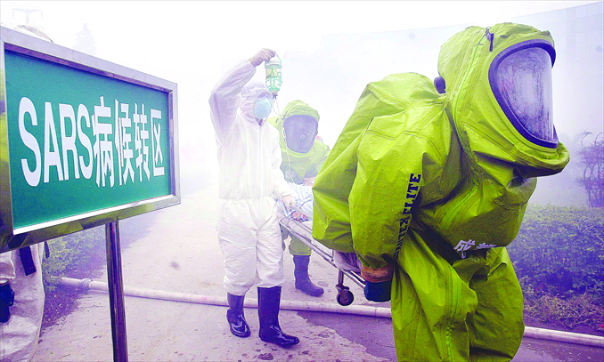 A stand-in SARS Patient is evacuated from a fire by emergency workers during a disaster training exercise at a designated SARS hospital in Chengdu, Sichuan Province in May 2003. Photo: CFP