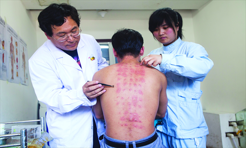 Doctors use tweezers to remove bee stingers from a patient's back. Photo:IC