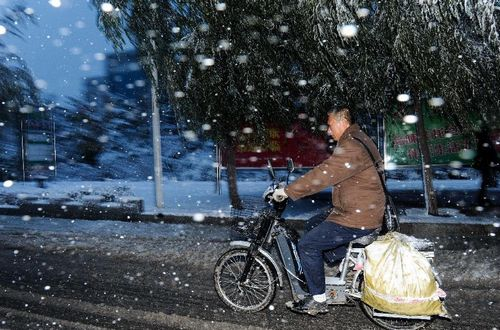 A man rides an electric vehicle on a snow-covered street in Changchun, capital of Northeast China's Jilin Province, October 22, 2012. Most parts of Jilin witnessed snowfall on Monday. Photo: Xinhua