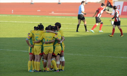 Players of the Beijing women's rugby sevens team form a ring on the field as their opponents, Shandong, continue playing during their final match on Tuesday at the Chinese National Games in Shenyang, Northeast China's Liaoning Province. Photo: CFP