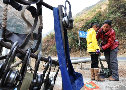 Residents from Shuangmidi Village make preparations before crossing the Nujiang River via a zip-line in Liuku County of Nujiang Lisu Autonomous Prefecture, southwest China's Yunnan Province, Feb. 2, 2013. More than 98 percent of Nujiang Lisu Autonomous Prefecture is occupied by mountains and valleys. The zip-lines have been quite popular transportation method along the Nujiang River since the ancient time. However, as transport conditions improve in recent years, a growing number of traditional zip-lines along the Nujiang River Valley have been dismantled or replaced by bridges. (Xinhua/Wang Changshan)