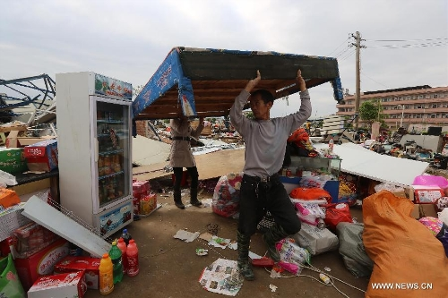 Locals salvage articles near a collapsed shed in Daoxian County, central China's Hunan Province, March 20, 2013. Three people were killed and 52 others were injured by a tornado that struck the county before dawn on Wednesday. The local meteorological observatory said the wind speed of the tornado reached 30.7 meters per second, a record for the observatory. (Xinhua/Guo Guoquan)