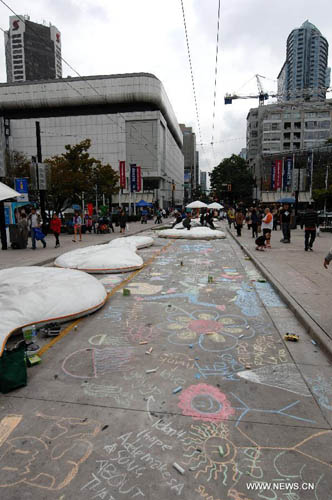 Chalk drawings adorn the pavement during first Chalkupy Vancouver event in Vancouver, Canada, on September 22, 2012. People from all walks of life descend on Robson Street in downtown Vancouver at noon to create beautiful sidewalk chalk art together. Photo: Xinhua