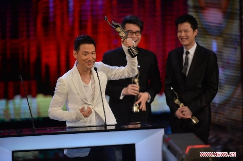 Singer Jacky Chang (L) lifts up the trophy after receiving the Best Original Film Song award by singing the song