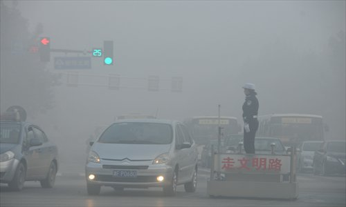 A policewoman stands in the middle of a smoggy street in Shijiazhuang, North China's Hebei Province on November 3. Photo: IC