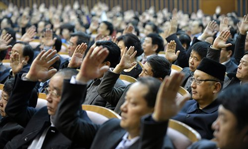 Deputies to the Xi'an People's Congress, Shaanxi Province, raise their hands Wednesday to approve the reports including the work report presented by the city government. Photo: CFP