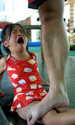 A girl cries as a coach stands on her legs to help stretch her ligaments at an amateur sports school in Nanning, Guangxi Zhuang Autonomous Region.