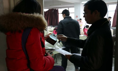 An examination supervisor checks a student's ID card before she enters the exam room on December 14, 2013 in Liaocheng, Shandong Province. Photo: CFP