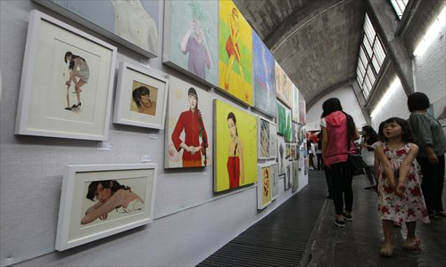 Visitors peruse the art at 798 Space (right). More often, these days, though, people come to 798 to stroll or tour the restaurants and streets than to seriously look at or buy art. Photos: CFP