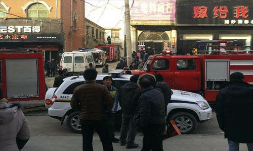 Rescue vehicles wait on the fire accident site in Lankao county, Central China's Henan Province, January 4, 2013. A fire broke out in a residential building in Chengguan township of Lankao county at about 8:30 am on Friday and was extinguished about two hours later. Four children were killed on the spot, three died on the way to hospital and one other is still being treated in the hospital. An initial investigation showed that the accident site was an adoptive family where the children killed and injured lived in. The cause of the fire is still under investigation. Photo: Xinhua