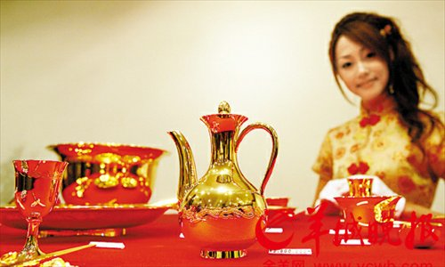 A model displays a set of Chinese tableware made of pure gold in Ginza, Tokyo on September 2, 2008. This set of tableware was valued at 6.3 million yuan ($1.02 million) at the time of the photograph. Photo: Xinhua