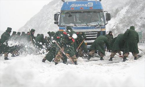 Armed police officers in Beijing clear up accumulated snow on the Beijing-Tibet Expressway early Sunday. Snowfall swept northern parts of China on the weekend including Beijing, Hebei and Shanxi, badly affecting the traffic. Photo: IC