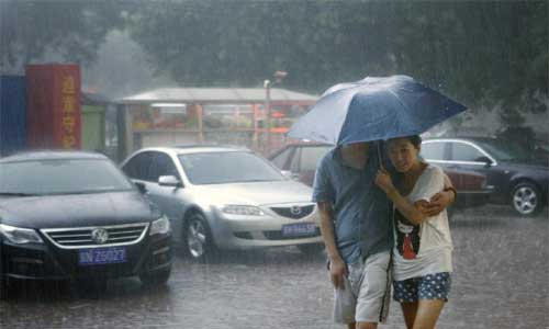 Pedestrians hold an umbrella as they walk amid heavy rain in Beijing, capital of China, July 21, 2012. Photo: Xinhua