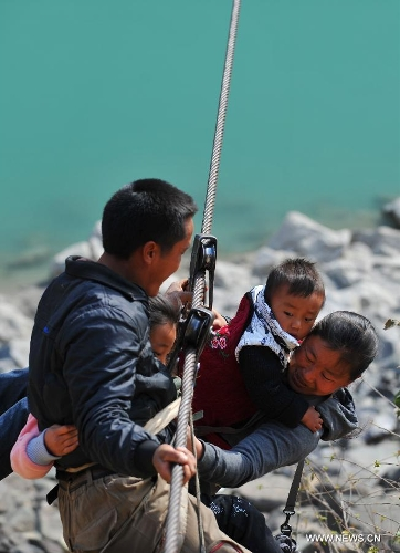 Residents from Shuangmidi Village cross the Nujiang River via a zip-line in Liuku County of Nujiang Lisu Autonomous Prefecture, southwest China's Yunnan Province, Feb. 2, 2013. More than 98 percent of Nujiang Lisu Autonomous Prefecture is occupied by mountains and valleys. The zip-lines have been quite popular transportation method along the Nujiang River since the ancient time. However, as transport conditions improve in recent years, a growing number of traditional zip-lines along the Nujiang River Valley have been dismantled or replaced by bridges. (Xinhua/Wang Changshan)