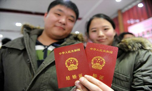 A couple show their marriage certificates at the marriage registration office in Zhengzhou, capital of Central China's Henan Province, January 4, 2013. Quite a number of couples flocked to tie the knot on January 4, 2013, or 2013/1/4, which sounds like
