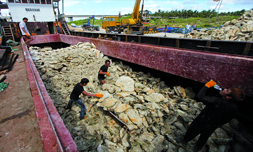 Workers offload clams from a fishing boat that is among the 12 boats intercepted by Philippine naval forces in April. Photo: Cai Xianmin/GT