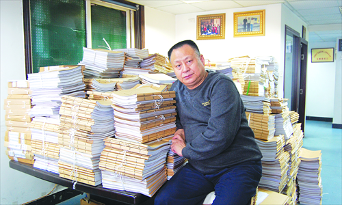 Zhou Litai leans against the piles of case files in his office in Chongqing.Photo: Courtesy Zhou Litai