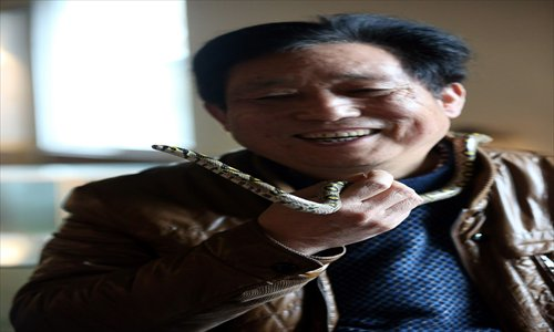 Yang Hongchang hangs out with his favorite snake. Photo: GT/Yang Hui
