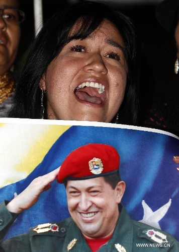 A resident reacts in front of Venezuela's Embassy to Ecuador, after the news of Venezuelan President Hugo Chavez's death was released, in Quito, Ecuador, on March 5, 2013. Venezuelan President Hugo Chavez died on March 5. (Xinhua/Santiago Armas)