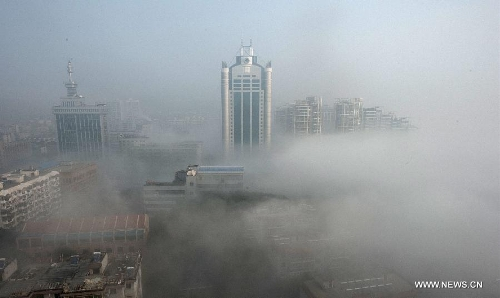 Buildings are seen amid dense fog in Wuhan City, capital of central China's Hubei Province, Jan. 12, 2013. (Xinhua/Cheng Min)