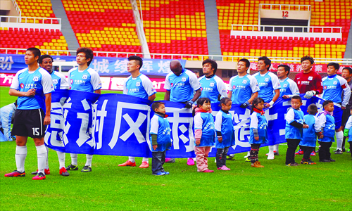 Players of Dalian Shide Football Club salute their fans at their last game on November 3 in Dalian, Liaoning Province, where the club is based. Photo: CFP