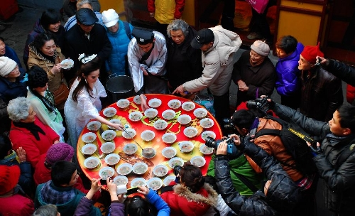 Citizens get porridge distributed by a performer acting as Madame White Snake, a white snake taking on a woman's form in a Chinese folk tale, at the Xuanzang Temple in Nanjing, capital of east China's Jiangsu Province, Jan. 19, 2013, to celebrate the traditional Laba Festival. Laba literally means the eighth day of the 12th lunar month. The Laba Festival is regarded as a prelude to the Spring Festival, or Chinese Lunar New Year, the most important occasion of family reunion, which falls on Feb. 10 this year. Eating porridge is an old tradition on the Laba Festival in China. Many temples also have the tradition of offering porridge to the public to commemorate Buddha and deliver his blessings to both believers and non-believers. (Xinhua/Li Xiang)