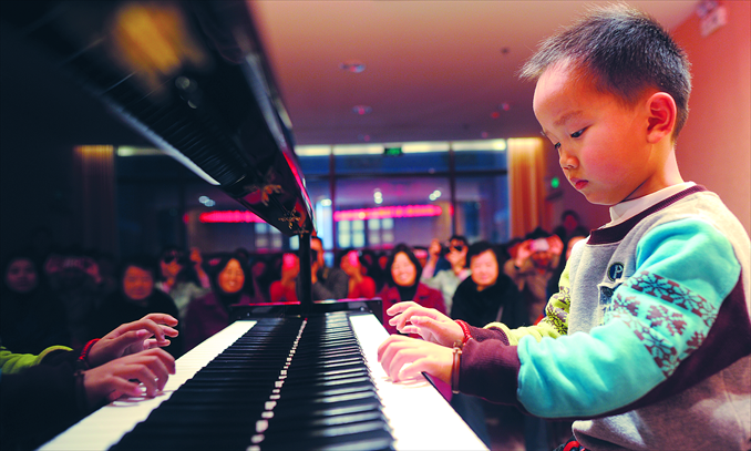 A kid plays the piano in front of an audience of adults in Wuhan, Hubei Province. Photo: CFP