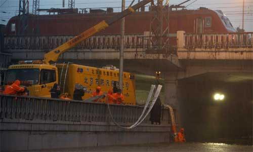 Worker drain the water at Lianhua Bridge in Beijing, capital of China, July 21, 2012. Photo: Xinhua