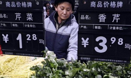 A consumer buys vegetable at a supermarket in Beijing, capital of China, December 9, 2012. China's consumer price index (CPI), a main gauge of inflation, grew 2 percent year on year in November, the National Bureau of Statistics announced Sunday. The inflation rate increased from a 33-month low of 1.7 percent in October as food prices increased. Photo: Xinhua