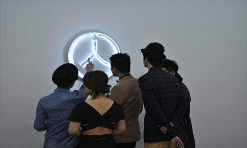 Visitors look at a neon wall artwork at the opening ceremony of the exhibition.