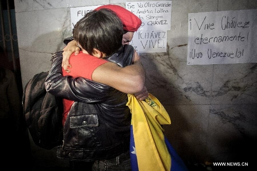 Residents hug with each other after the news of Venezuelan President Hugo Chavez's death was released, in Mexico City, capital of Mexico, on March 5, 2013. Venezuelan President Hugo Chavez died on March 5. (Xinhua/Pedro Mera)