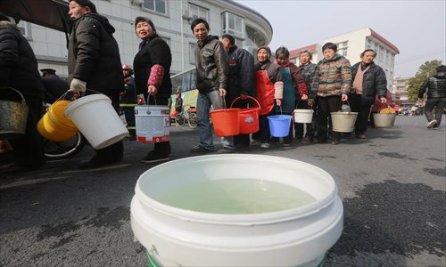 Residents in Songjiang district of Shanghai line up to get water supplies from a fire engine on Friday. Photo: CFP