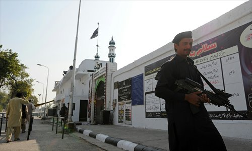 A Pakistani security serviceman stands guard near a Shiite Muslim mosque following overnight suicide bomb attacks on minority Shiite Muslims, in Islamabad on Thursday. Photo: AFP