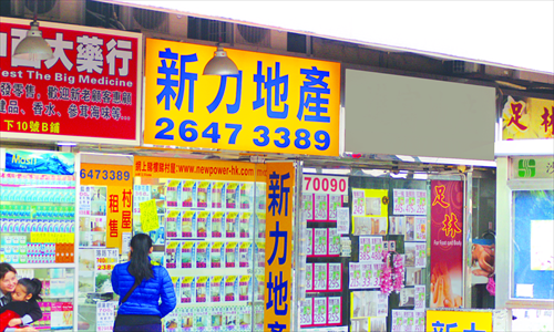 A woman walks past property advertisements posted by real estate agencies in Sha Tin New Town, Hong Kong. Photo: Song Shengxia/GT