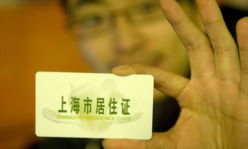 A man displays his Shanghai residence card. For nonlocals, having a residency permit now means their children can attend the same schools as Shanghai children and enjoy many of the same welfare benefits. Photo: CFP
