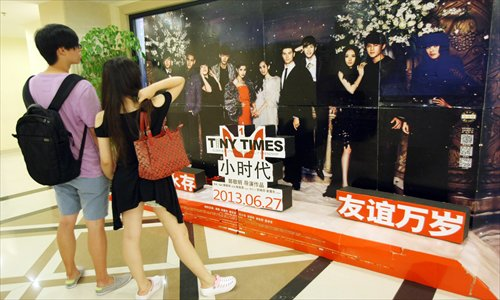 Moviegoers walk past a promotional poster for the film Tiny Times. The film has spurred controversy over its depiction of materialism. Photo: CFP