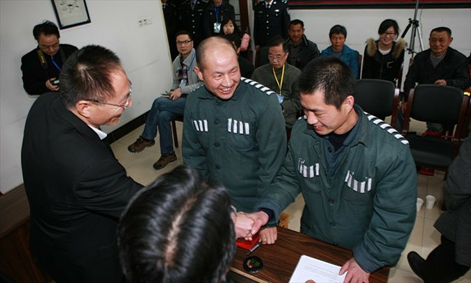 An officer with Zhejiang People's High Court conveys apologies to Zhang Gaoping and his nephew after they are freed. Photo: Zhejiang People's High Court